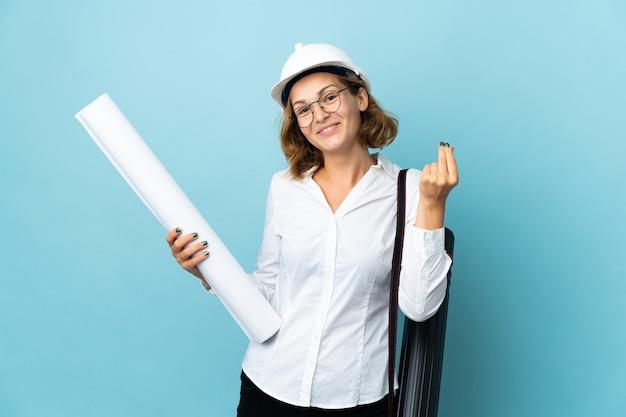 Giovane architetto georgiano donna con casco e azienda blueprint su sfondo isolato che fa gesto di denaro