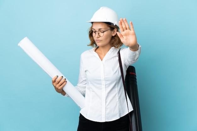 Giovane architetto georgiano donna con casco e azienda blueprint su sfondo isolato facendo gesto di arresto e deluso