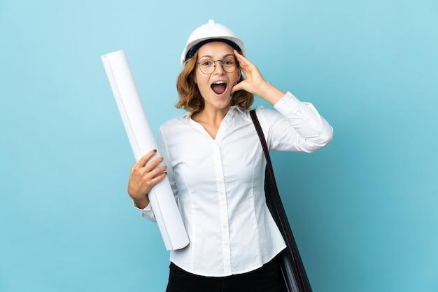Giovane donna georgiana architetto con casco e azienda blueprint su sfondo isolato con espressione di sorpresa