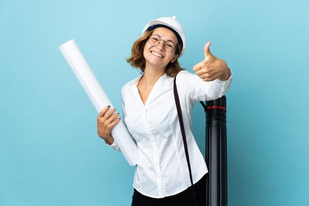 Giovane donna georgiana dell'architetto con il casco e che tiene le cianografie sopra la parete isolata con i pollici in su perché qualcosa di buono è accaduto