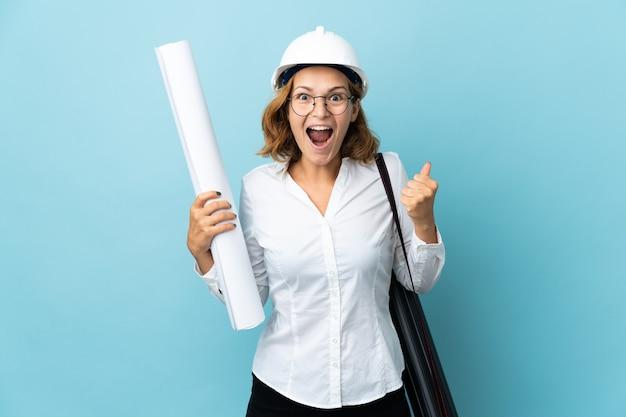 Giovane donna georgiana dell'architetto con il casco e le cianografie della holding isolate