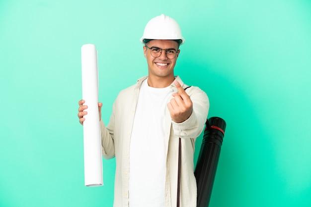 Giovane uomo dell'architetto che tiene i modelli sopra fondo isolato che fa il gesto imminente