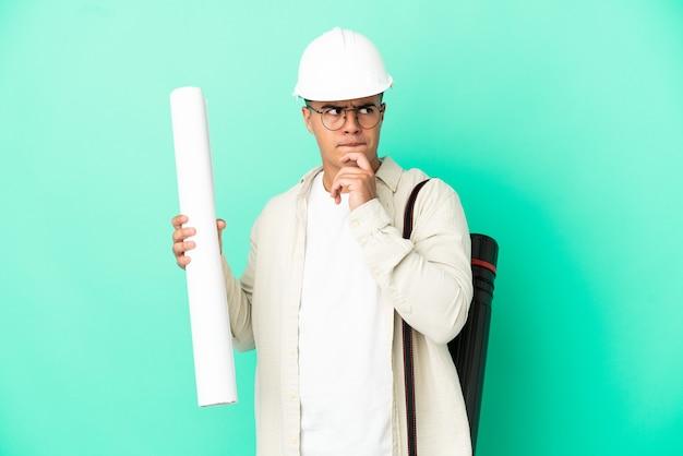 Giovane architetto uomo con progetti su sfondo isolato avendo dubbi e pensando