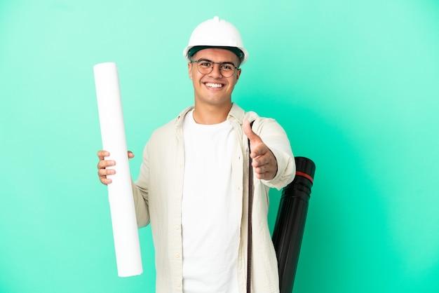 Giovane architetto uomo con progetti su sfondo isolato stringendo la mano per la chiusura di un buon affare