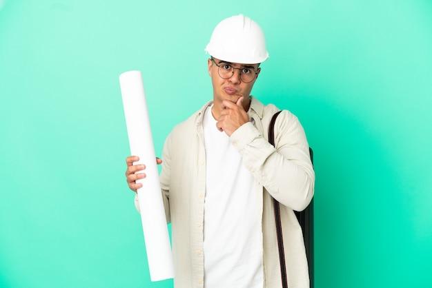 Giovane uomo dell'architetto che tiene i modelli sopra il pensiero isolato del fondo