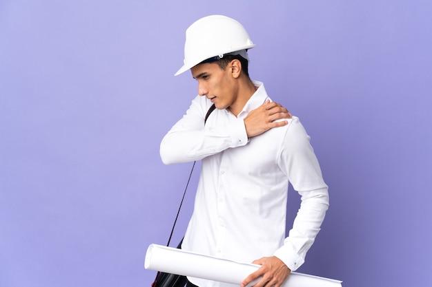 Giovane uomo architetto isolato che soffre di dolore alla spalla per aver fatto uno sforzo