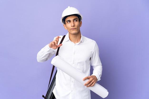 Uomo giovane architetto isolato con le dita incrociate e augurando il meglio