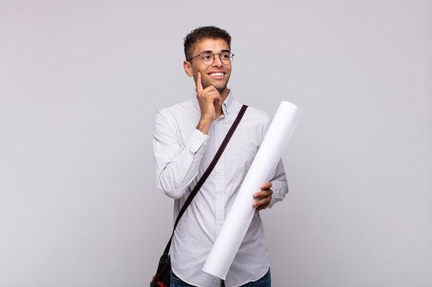 Uomo giovane architetto sorridente felicemente e fantasticando o dubitando, guardando al lato