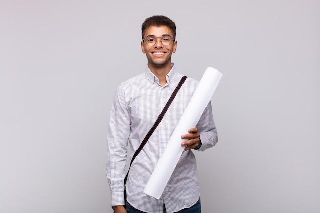 Uomo giovane architetto sorridente felicemente con una mano sull'anca e atteggiamento fiducioso, positivo, orgoglioso e amichevole