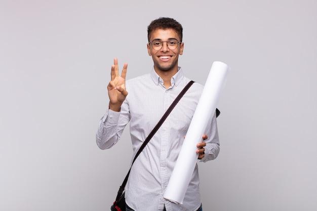 Uomo giovane architetto sorridente e guardando amichevole, mostrando il numero tre o terzo con la mano in avanti, conto alla rovescia