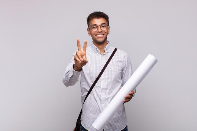 Giovane architetto che sorride e sembra felice, spensierato e positivo, gesticolando vittoria o pace con una mano