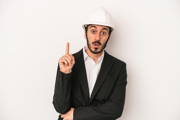 Giovane architetto che indossa un casco da costruzione isolato su sfondo bianco con qualche grande idea, concetto di creatività.