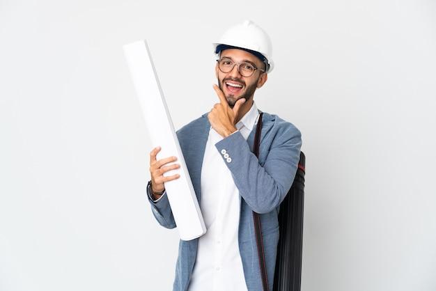 Uomo giovane architetto con casco e azienda schemi isolati su sfondo bianco felice e sorridente