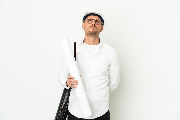 Giovane architetto uomo con casco e tenendo progetti isolati su sfondo bianco e guardando in alto