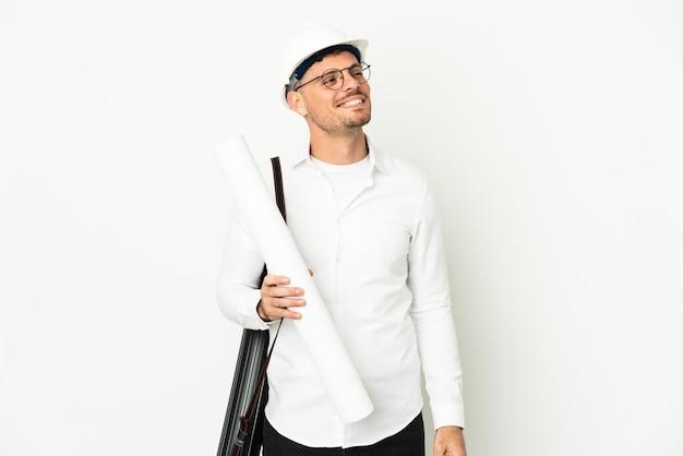 Giovane uomo dell'architetto con il casco e che tiene le cianografie isolate su fondo bianco che pensa un'idea mentre osserva in su
