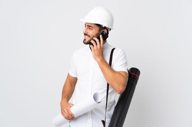 Uomo giovane architetto con casco e tenendo schemi isolati su bianco mantenendo una conversazione con il telefono cellulare con qualcuno
