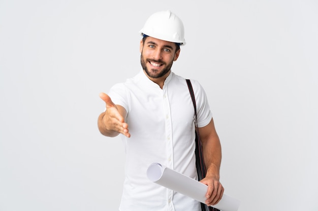 Uomo giovane architetto con casco e tenendo i modelli isolati su bianco che agitano le mani per chiudere un buon affare
