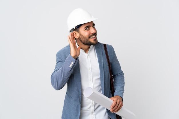Uomo del giovane architetto con il casco e che tiene le cianografie isolate sulla parete bianca che ascolta qualcosa mettendo la mano sull'orecchio