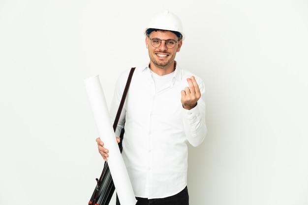 Uomo del giovane architetto con il casco e che tiene le cianografie isolate sulla parete bianca che fa gesto dei soldi