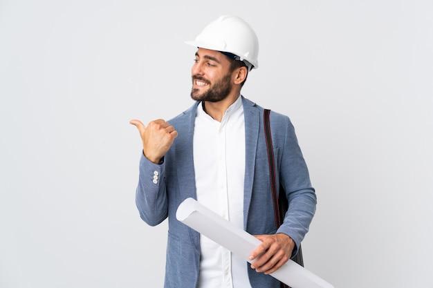 Uomo giovane architetto con casco e holding schemi isolati sul muro bianco che punta verso il lato per presentare un prodotto
