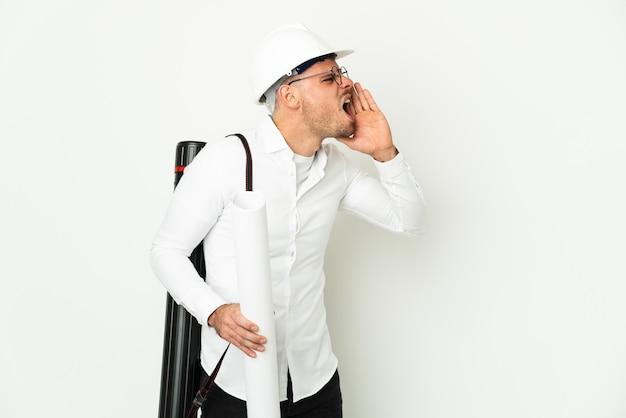 Uomo giovane architetto con il casco e che tiene le cianografie isolate sul muro bianco che grida con la bocca spalancata a lato