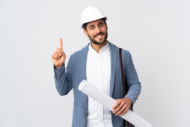 Uomo giovane architetto con casco e tenendo schemi isolati sulla parete bianca che mostra e alzando un dito in segno del meglio