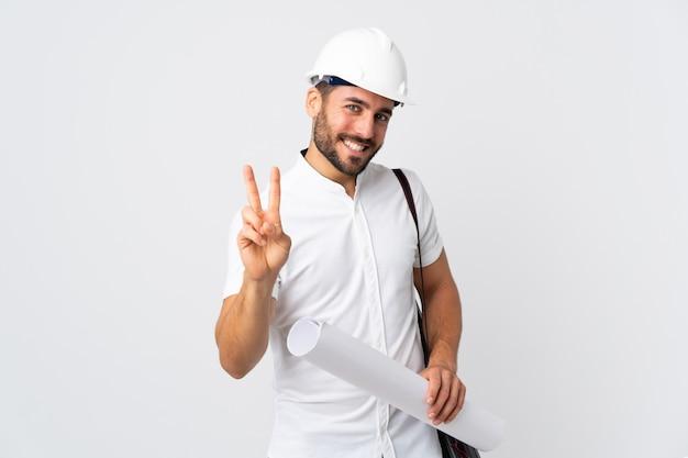 Giovane uomo dell'architetto con il casco e giudicare i modelli isolati sulla parete bianca che sorride e che mostra il segno di vittoria