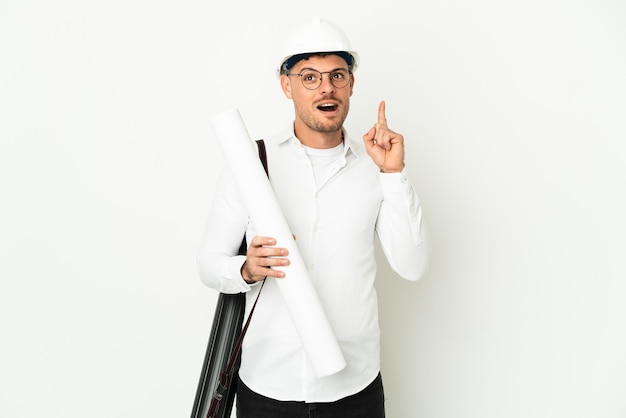 Uomo del giovane architetto con il casco e che tiene le cianografie isolate sulla parete bianca che pensa un'idea che indica il dito verso l'alto