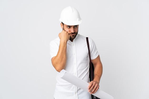Giovane uomo dell'architetto con il casco e giudicare i modelli isolati sulla parete bianca con l'espressione stanca e annoiata