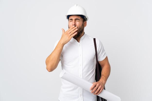 Uomo del giovane architetto con il casco e che tiene i modelli isolati sul muro bianco che sbadiglia e che copre la bocca spalancata con la mano