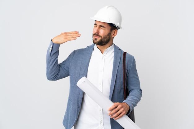 Giovane uomo dell'architetto con il casco e giudicare i modelli isolati su bianco con l'espressione stanca e malata