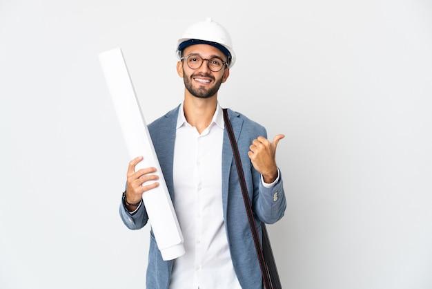 Uomo giovane architetto con casco e azienda schemi isolati