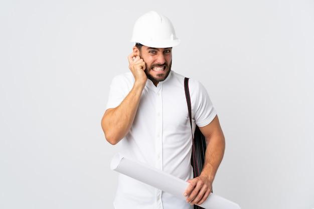 Giovane uomo dell'architetto con il casco e la tenuta dei modelli sulla parete bianca frustrata e che copre le orecchie