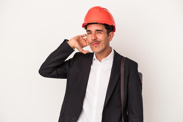 Giovane architetto uomo di razza mista isolato su sfondo bianco toccando la parte posteriore della testa, pensando e facendo una scelta.