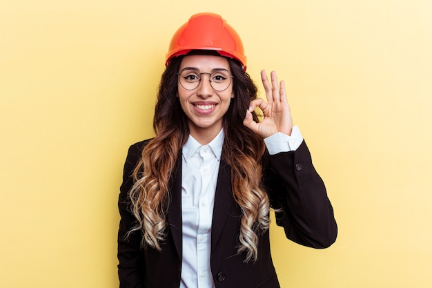Giovane architetto donna di razza mista isolata su sfondo giallo allegro e fiducioso che mostra gesto ok.