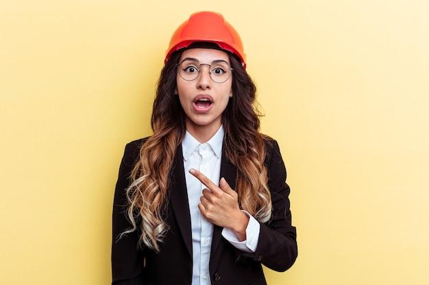 Giovane architetto donna di razza mista isolata su sfondo giallo che punta al lato