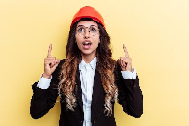 Giovane donna di razza mista architetto isolata su sfondo giallo che punta al rialzo con la bocca aperta.