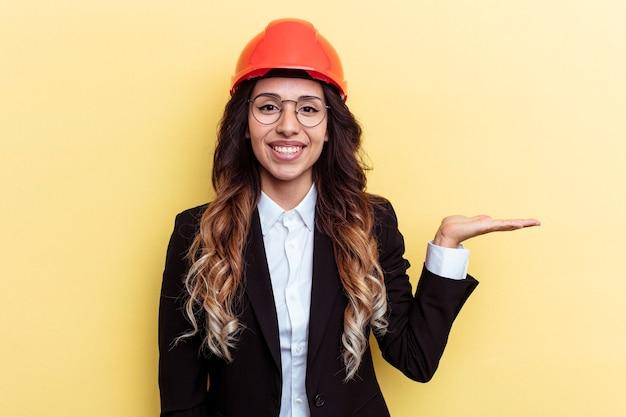 Giovane donna di razza mista architetto isolata su sfondo giallo che mostra uno spazio di copia su un palmo e tiene un'altra mano sulla vita.