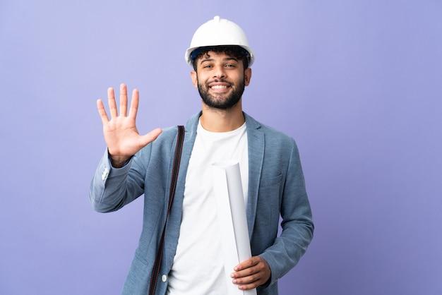 Giovane architetto marocchino uomo con casco e azienda schemi sopra isolati contando cinque con le dita