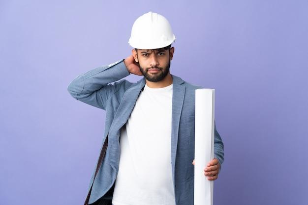 Giovane architetto marocchino uomo con casco e azienda schemi sopra isolati avendo dubbi