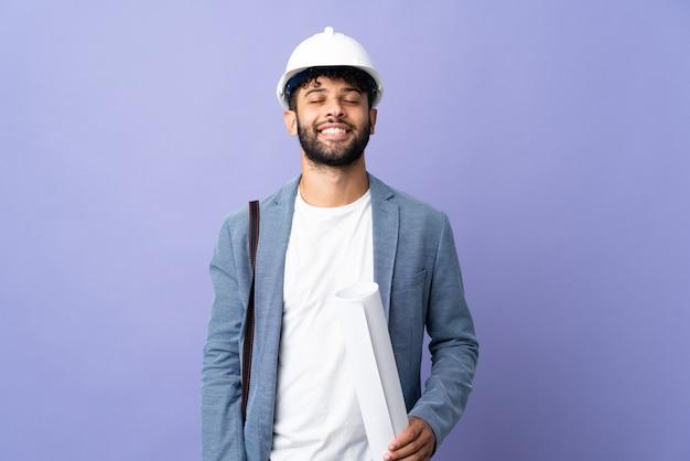 Uomo marocchino del giovane architetto con il casco e che tiene i modelli sopra la risata isolata