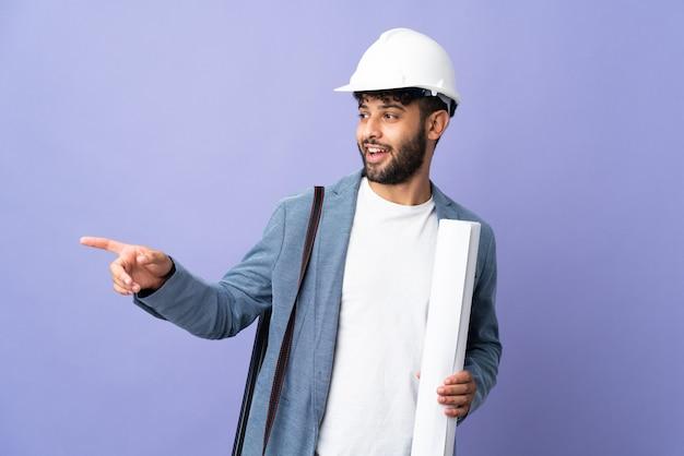 Uomo marocchino del giovane architetto con il casco e che tiene le cianografie sopra il dito puntato isolato al lato e che presenta un prodotto