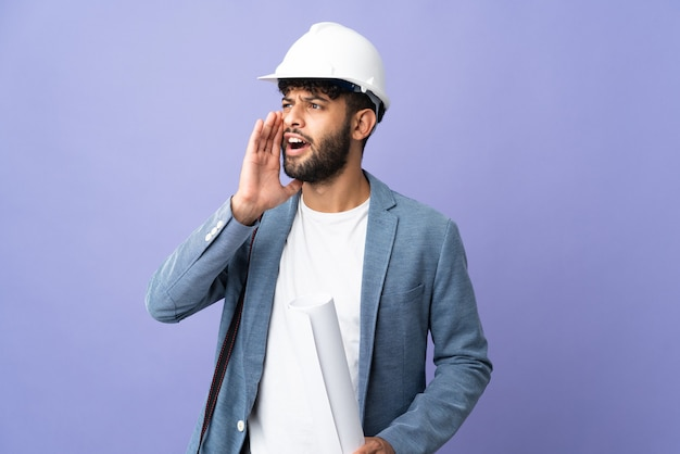 Giovane architetto marocchino uomo con casco e in possesso di schemi sopra isolato gridando con la bocca spalancata di lato