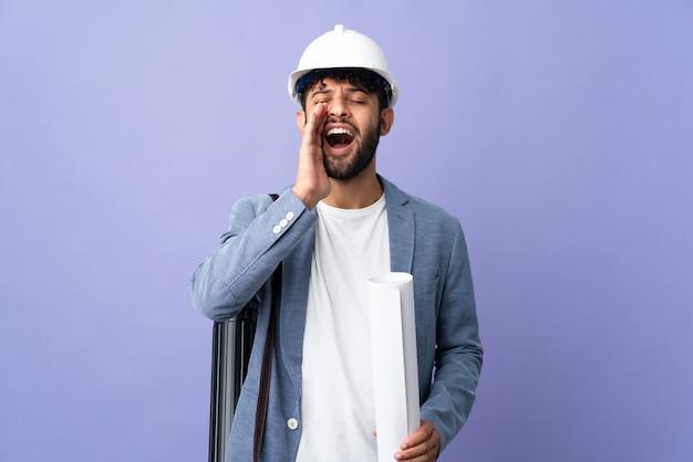Uomo marocchino del giovane architetto con il casco e che tiene i modelli sopra gridando isolato con la bocca spalancata