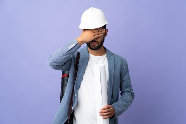 Uomo marocchino del giovane architetto con il casco e che tiene i modelli sopra gli occhi isolati della copertura murale con le mani. non voglio vedere qualcosa