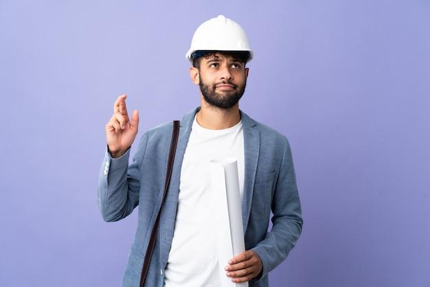 Giovane architetto marocchino uomo con casco e tenendo le cianografie isolate con le dita che si incrociano e che desiderano il meglio