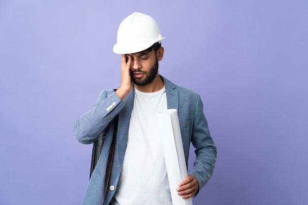 Giovane architetto marocchino uomo con casco e azienda schemi sopra isolati con mal di testa
