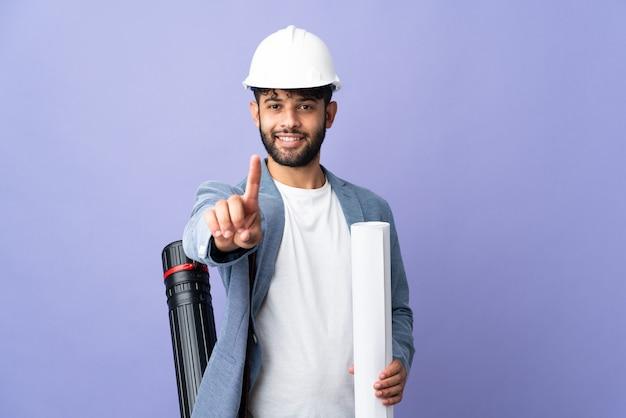 Uomo marocchino del giovane architetto con il casco e le cianografie della holding isolate
