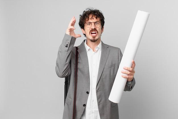 Giovane architetto che urla con le mani in alto