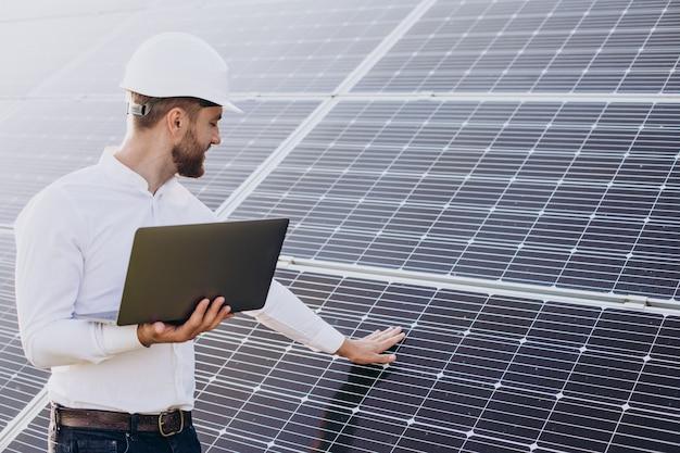 Giovane architetto in piedi accanto a pannelli solari che eseguono diagnosi sul computer